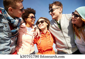 smiling friends in sunglasses laughing on street