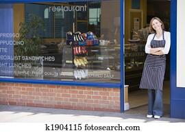 Woman standing in doorway of restaurant smiling