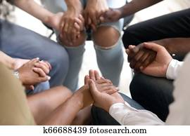 Diverse people sitting in circle holding hands at group therapy