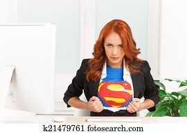 serious woman shows her superman uniform underneath her clothes. Super businesswoman sitting in office and tearing her clothes