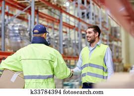 men in safety vests shaking hands at warehouse