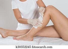 Beautician Waxing Leg Of Woman