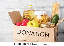 Donation of food collected in a box. Gray background. Copy space.