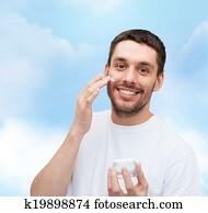 beautiful smiling man applyin cream