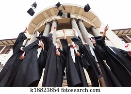 group of graduates throwing graduation hats in the air