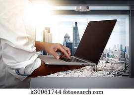 businessman working on his laptop in office with london city background