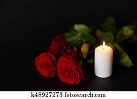 red roses and burning candle over black background