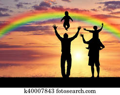 Pair of gay men and their children playing at sunset