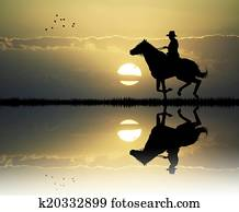 cowboy with lasso at sunset