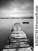 Looking over a desolate pier and a boat, black and white