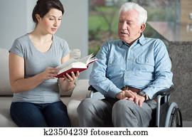 Senior care assistant reading book