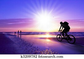 mountain biker on beach and sunset