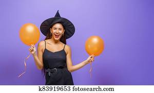 Young woman in black witch costume