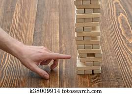 Close-up hands of man pulls out wooden bricks Stock Image