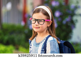 9faa485dc1d6 Pretty little 9 year old girl walking back to school, wearing glasses and  blue backpack
