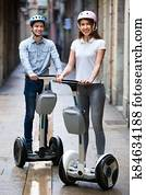 Positive boy and girl posing on segways in vacation