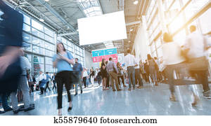 Blurred trade fair visitors walking in hall