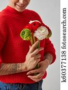Beautiful girl in a red sweater with flowers in hands on a white background