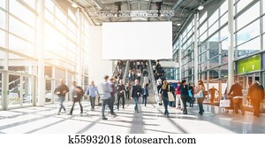 large crowd of anonymous blurred people at a trade show, including copy space banner