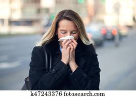 Woman with a seasonal winter cold blowing her nose