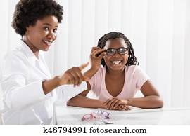 Smiling Girl Wearing Eyeglasses In Front Of Optometrist