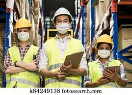 Interracial warehouse worker team with face mask