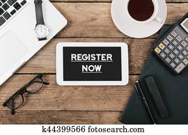 Register Now text on tablet computer on office desk