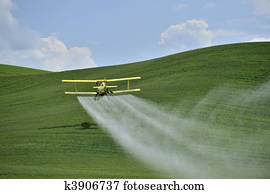 Biplane Crop Duster spraying a farm field.