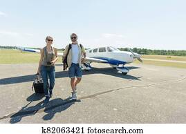 rich young couple departing from private plane