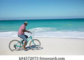Old man with a bike at the beach