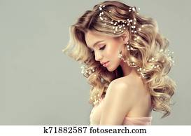 Pretty woman with soft smile on the face is demonstrating long and curly hairstyle.