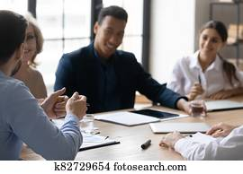 Interested diverse employees listening to mentor coach at meeting