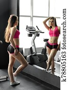 Young pretty sexy female posing in front of large mirror in gym. Heathy lifestyle, sport conception.