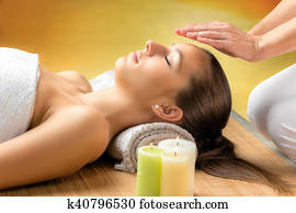 Woman receiving reiki treatment on forehead.