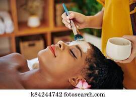 Woman geting purifying clay mask