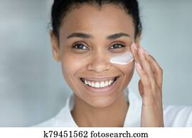 Close up face african beautiful woman apply cream on skin