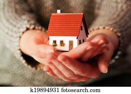 Woman holding a small new house in her hands. Real estate, mortgage