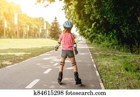 Little girl roller skating in park