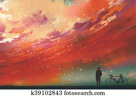 man standing against red clouds