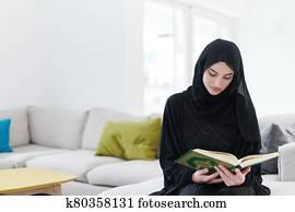 young muslim woman reading Quran at home