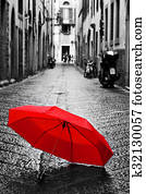 Red umbrella on cobblestone street in the old town. Wind and rain
