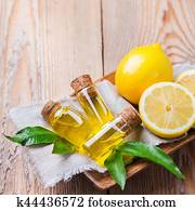 Organic essential lemon oil with green leaves and fruit