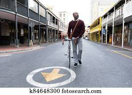 African American man walking beside his bike in the city street