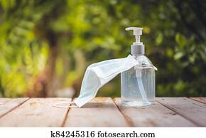 Face mask and white hand sanitizer or alcohol gel pump bottle on wooden top with green nature backgrounds