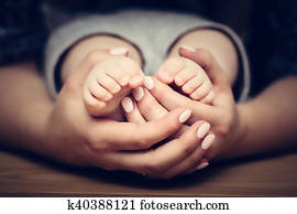 Little baby feet in mother's hands. Child care, feeling safe, protect.