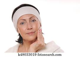 portrait of pretty senior woman taking off makeup