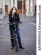 Caucasian woman wearing a protective mask on her bike, wearing earphones in the streets