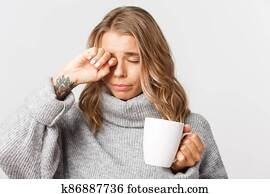 Close-up of beautiful sleepy woman with tatoos, drinking coffee from mug and rubbing eyes, standing over white background