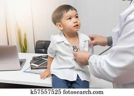 Pediatrician doctor examining a little asian boy by stethoscope