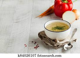 Homemade broth in a white bowl on a napkin with dill and fresh vegetables on a wooden background. Copy space.
